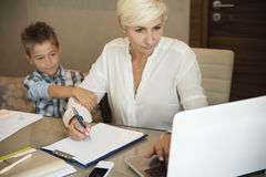 Concentrated  businesswoman with her young son disturbing her. Businesswoman  working on laptop while her young son in asking for attention Royalty Free Stock Photo