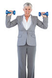 Concentrated businesswoman holding dumbbells Royalty Free Stock Image