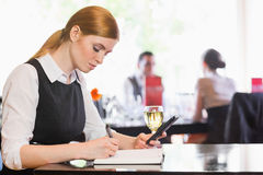 Concentrated businesswoman holding phone while writing Royalty Free Stock Images