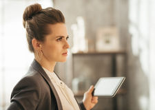 Concentrated businesswoman holding tablet in loft apartment Royalty Free Stock Image