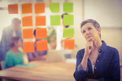 Concentrated businesswoman looking post its on the wall Stock Photography