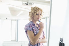 Concentrated businesswoman looking at presentation board in creative office Stock Photo