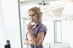 Concentrated businesswoman looking at presentation board in creative office Royalty Free Stock Photo
