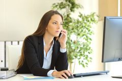 Concentrated businesswoman on the phone. Concentrated businesswoman talking on the phone and checking information in a desktop computer Royalty Free Stock Photo