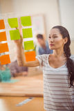 Concentrated businesswoman pointing post its on the wall Stock Photography