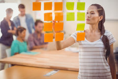 Concentrated businesswoman pointing post its on the wall. In the office Royalty Free Stock Image