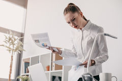 Concentrated businesswoman reading business documents in office Stock Photo