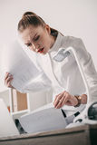 Concentrated businesswoman reading contract documents in office Royalty Free Stock Photos