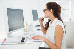 Concentrated businesswoman using computer monitor Royalty Free Stock Images