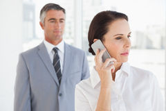 Concentrated businesswoman using her phone Royalty Free Stock Images