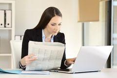 Businesswoman working reading a newspaper stock photo