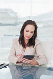 Concentrated businesswoman working on her tablet pc Stock Images
