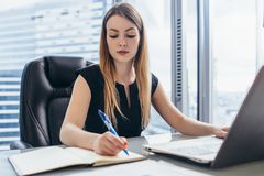 Concentrated businesswoman working writing notes in notebook sitting at desk in office stock photos