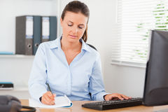 Concentrated businesswoman writing Stock Photo