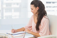 Concentrated businesswoman writing on clipboard Royalty Free Stock Images