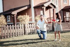 Concentrated caring dad looking at his daughter holding paper planes. stock photography