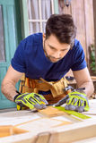 Concentrated carpenter in protective gloves measuring cut of wooden plank Royalty Free Stock Photo