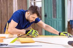 Concentrated carpenter in protective gloves taking measures of wooden plank. Side view of concentrated carpenter in protective gloves taking measures of wooden Stock Photo