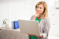 Concentrated casual businesswoman working with laptop Royalty Free Stock Photography