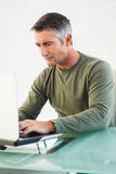 Concentrated casual man using laptop Royalty Free Stock Images