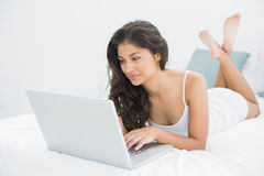 Concentrated casual woman using laptop in bed Stock Photos