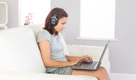 Concentrated casual woman working with her notebook while listening to music Stock Photos