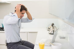 Concentrated casual young man using laptop in kitchen Royalty Free Stock Photos