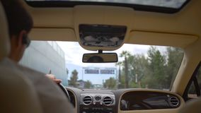 Concentrated chauffeur driving luxury car in urban traffic, business driver. Stock footage stock video
