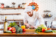 Concentrated chef cook standing and cutting fresh vegetables Stock Photos