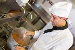 Concentrated chef preparing food in the kitchen. Side view of a concentrated male chef preparing food in the kitchen stock photography