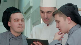 Concentrated chef showing his trainees something on digital tablet stock video
