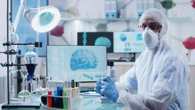 Concentrated chemist wearing protective mask, clothes and glasses looks at the camera. Modern research center with displays showing 3D scans of brain and DNA stock video