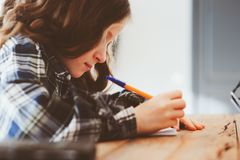Concentrated child girl doing homework. Thoughtful school kid thinking and looking for an answer Royalty Free Stock Photo