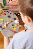 Concentrated child mixing colors in the art studio. Process of mixing colors. Attentive gifted involved child sitting in the art studio and having art class Royalty Free Stock Images