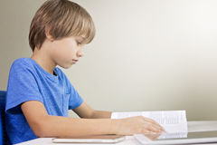 Concentrated child reading a book. Mobile phone and tablet computer are on the table near him. Technology, education Royalty Free Stock Photo