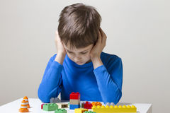 Concentrated child sitting and looking down to colorful plastic construction toy blocks at the table Stock Image