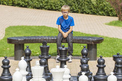 Concentrated child, thinking about his next move, sitting on a wooden bench during an outdoor chess game using life sized pieces a Royalty Free Stock Photography