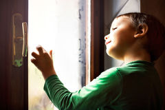Concentrated child writes with his fingers on the foggy window Royalty Free Stock Photos