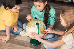 Concentrated children exploring globe in library Stock Photos