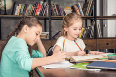 Concentrated classmates doing homework together in library Royalty Free Stock Photos