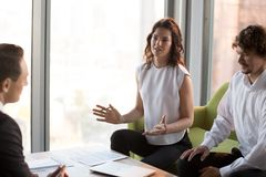 Diverse colleagues talk discussing project at casual meeting. Concentrated colleagues or workers discuss startup project, consider paperwork at briefing together stock photography