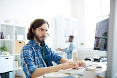 Concentrated computer programmer in office. Serious concentrated hipster young bearded computer programmer working with two desktop computers and typing on royalty free stock images