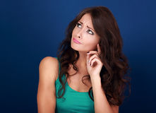 Concentrated confused beautiful woman thinking and looking up on Stock Images