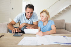 Concentrated couple with bills and calculator in living room Royalty Free Stock Images