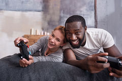 Concentrated couple enjoying games with console in bed. We will win. Concentrated young international couple enjoying games ad using console while lying in bed Stock Image