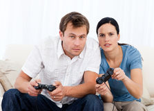Concentrated couple playing video games together. On the sofa at home Stock Images