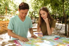 Concentrated couple sitting outdoor. By the table with map Royalty Free Stock Images