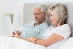 Concentrated couple using digital tablet in bed Stock Image