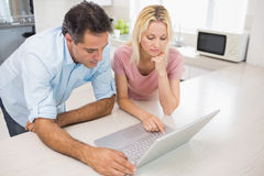 Concentrated couple using laptop in kitchen Royalty Free Stock Photo