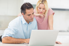 Concentrated couple using laptop in kitchen Stock Images